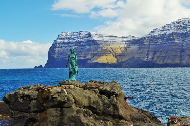 Figura Selkie czyli kobiety-foki wmiejscowości Mikladalur nawyspie Kalsoy. Wtle wyspa Kunoy. Wyspy Owcze, Hit The Road Travel