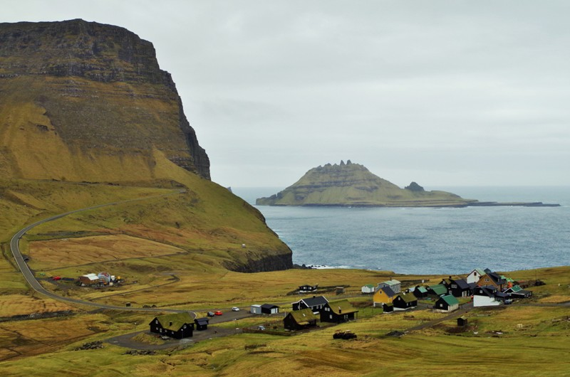 A view of picturesque rock formations of the Vágar Island seen from Gásadalur. The Faroe Islands - Hit The Road Travel