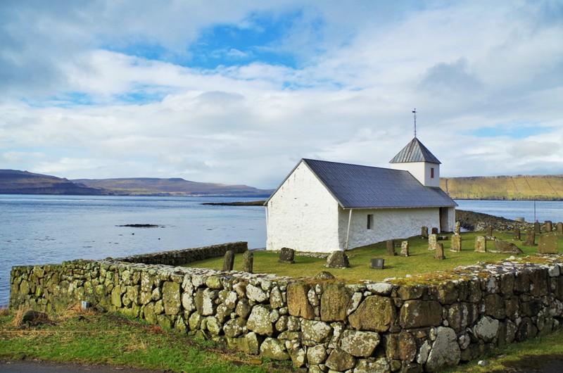 Kościół Św. Olafa wmiejscowości Kirkjubøur nawyspie Streymoy. Wtle wyspy Hestur iSandoy. Wyspy Owcze - Hit The Road Travel